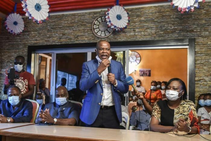 L'ancien ministre du Budget, Justin Katinan Koné (c) fait une déclaration à son arrivée à Abidjan après dix ans d'exil, le 30 avril 2021. SIA KAMBOU / AFP