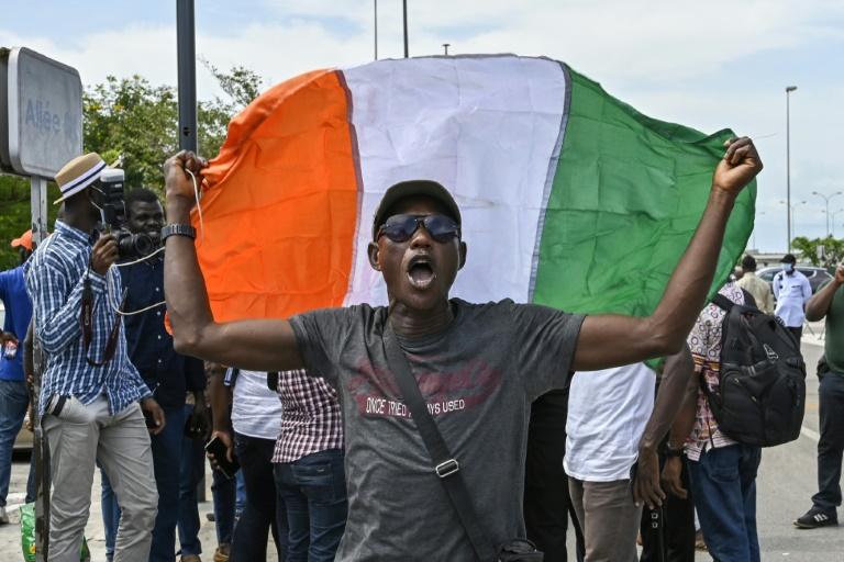 Un homme déploie le drapeau ivoirien pour le retour au pays de partisans de l'ex-président Laurent Gbagbo après dix ans d'exil, le 30 avril 2021 à Abidjan.  Crédit Photo : SIA KAMBOU